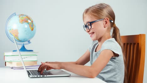 Portrait-Student-7-8-Years-Old-Typing-Text-On-Laptop-And-Sitting-In-The-Table