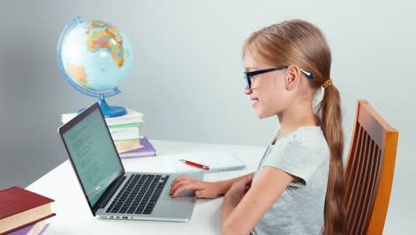 Porträtstudent-7-8-Jahre-Alt-Mit-Laptop-Und-Am-Tisch-Sitzend