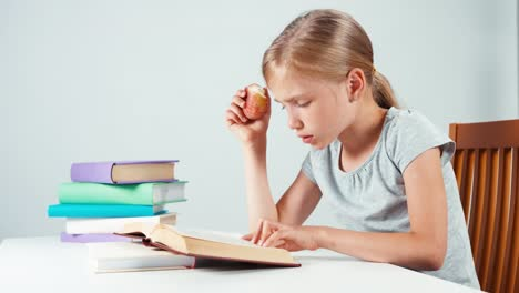 Portrait-Student-Girl-Child-7-8-Years-Reading-Textbook-And-Eating-Fruit