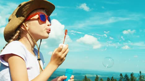 Portrait-Tourist-Blowing-Soap-Bubbles-Against-The-Mountain-And-Laughing