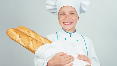 Portrait-Young-Baker-Girl-7-8-Years-Holds-Long-Loaves-Smiling-At-Camera-Ok