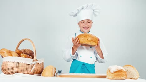 Portrait-Young-Baker-Girl-Breaks-Loaf-Of-Bread-Gives-You-One-Piece-At-Camera