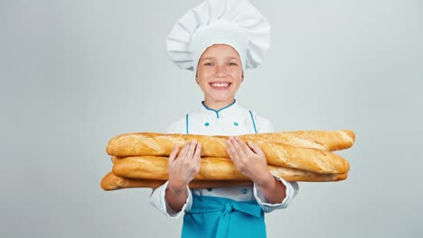 Portrait-Young-Baker-Girl-Child-Holds-Bread-Baguettes-And-Smiling-At-Camera