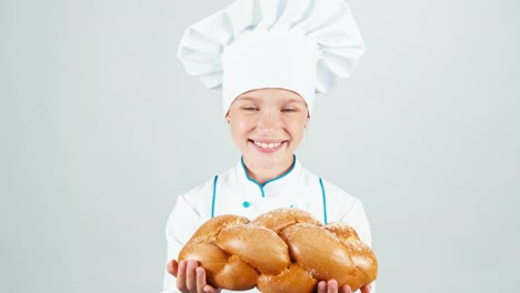 Portrait-Young-Baker-Holds-Braided-Bread-And-Gives-Loaf-You-At-Camera-Smiling