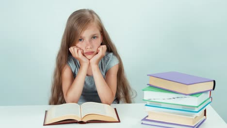 Sad-Schoolgirl-7-8-Years-Old-Reading-Book-On-The-Table-And-Looking-At-Camera