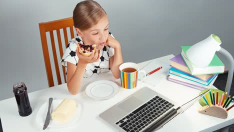 School-Girl-7-8-Years-Eating-Sandwich-With-Butter-And-Jam-Sitting-At-The-Desk