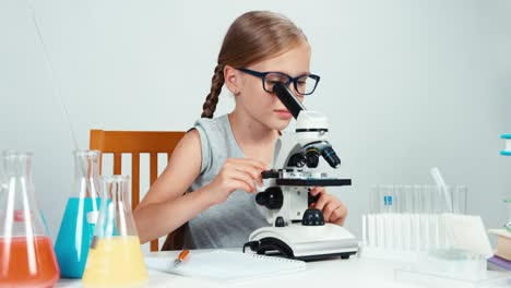 Niña-De-La-Escuela-7-8-Años-Con-Gafas-Usando-Microscopio-Y-Algo-Escrito