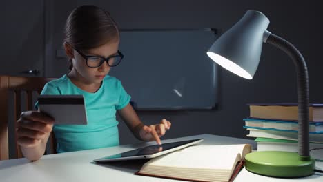 School-Girl-7-8-Years-Old-Using-Credit-Card-And-Tablet-PC-In-The-Night