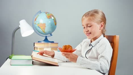 School-Girl-7-8-Years-Reading-Book-And-Eating-Muffin
