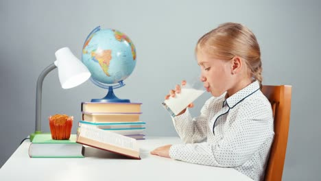 School-Girl-7-8-Years-Reading-Book-Sitting-At-The-Table-On-White-Background