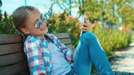 School-Girl-7-8-Years-Using-Smartphone-Laughing-And-Sitting-On-The-Bench-02
