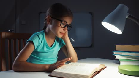 School-Girl-7-8-Years-Yawns-And-Reading-A-Book-In-The-Night-In-Her-Desk