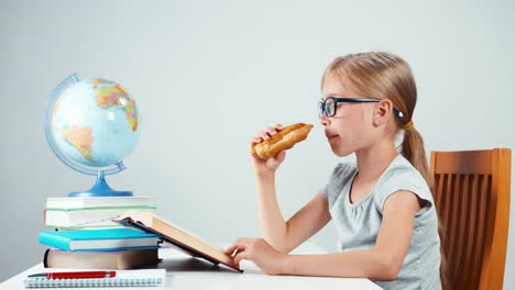 School-Girl-Glasses-Reading-Textbook-And-Eating-Croissant