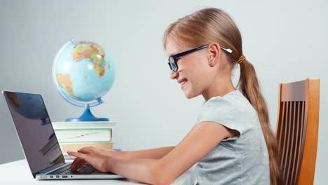 School-Girl-Glasses-Typing-In-Her-Laptop-Sitting-At-Desk-Isolated-On-White