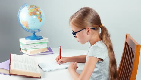 School-Girl-Glasses-Writing-In-Her-Notebook-And-Smiling-At-Camera