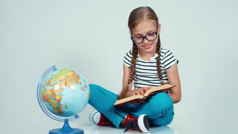 School-Girl-Reading-Book-Near-Globe-And-Smiling-At-Camera-Isolated-On-White