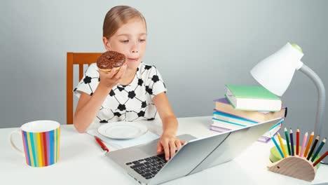 Niña-De-La-Escuela-Escribiendo-Algo-En-Su-Computadora-Portátil-Y-Comiendo-Donuts-Sentado-En-El-Escritorio