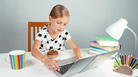 School-Girl-Typing-Something-In-Her-Laptop-And-Rubs-Hands-Sitting-At-The-Desk