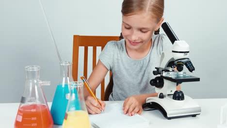 Niña-De-La-Escuela-Con-Microscopio-Y-Algo-Escrito-En-Su-Cuaderno-Aislado