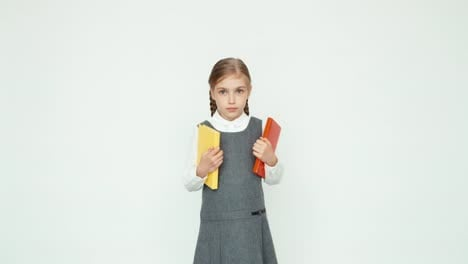 Schoolgirl-7-8-Years-Holding-Books-And-Looking-At-Camera