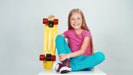 Schoolgirl-7-8-Years-Old-Holds-Penny-Skateboard-And-Sitting-On-The-Floor