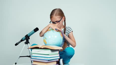Schoolgirl-7-8-Years-Using-Her-Globe-And-Looking-At-Camera-Sitting-On-The-Floor
