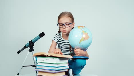 Schoolgirl-7-8-Years-Using-Her-Globe-And-Reading-Book-Sitting-On-The-Floor