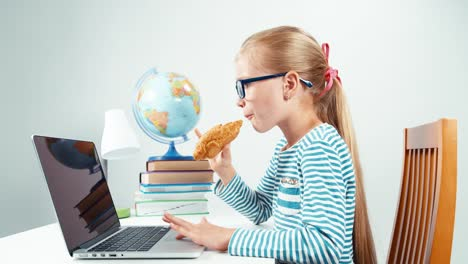 Schoolgirl-Child-7-8-Years-Using-Her-Laptop-And-Eating-Croissant