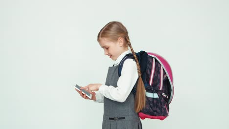 Schoolgirl-with-backpack-using-her-mobile-phone-and-smiling
