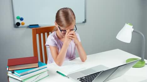 Schoolgirl-Doing-Homework-In-Mathematics-I-Her-Desk-With-Help-Of-Laptop