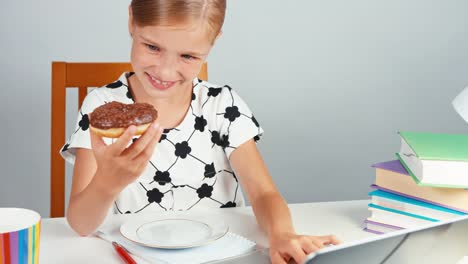 Schoolgirl-Eating-Donut-And-Using-Her-Laptop-And-Sitting-At-The-Desk
