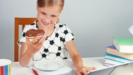 Colegiala-Comiendo-Donuts-Y-Usando-Su-Computadora-Portátil-Y-Sentado-En-El-Escritorio