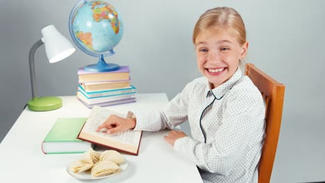 Schoolgirl-Eating-Potato-Chips-And-Reading-Textbook-At-The-Table-In-The-Evening-01