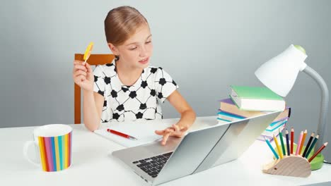 Schoolgirl-Holds-Her-Lollipop-And-Typing-Something-In-Her-Laptop
