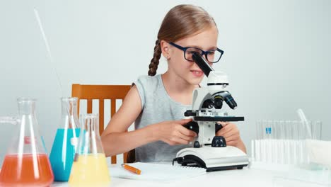 Schoolgirl-Sitting-In-The-Desk-Near-Microscope-And-Smiling-At-Camera-With-Teeth