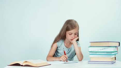Schoolgirl-Writing-In-Her-Notebook-Child-Girl-Sitting-At-The-Table-On-White