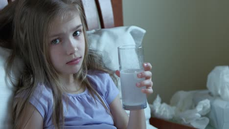 Krankes-Mädchen-7-Jahre-Alt-Das-Aspirin-Trinkt-Und-Auf-Dem-Bett-Unter-Dem-Rohling-Sitzt-Sitting