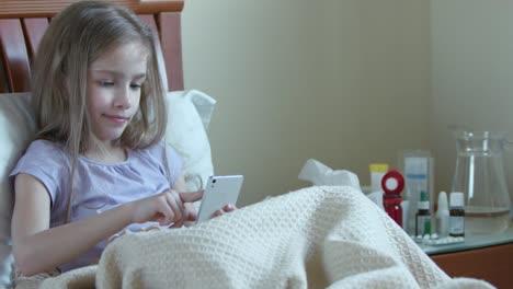 Niña-Enferma-De-7-Años-Con-Teléfono-Inteligente-Y-Sonriendo-A-La-Cámara