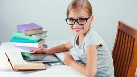 Student-Girl-7-8-Years-Old-Using-Tablet-PC-In-Her-Desk-And-Looking-At-Camera
