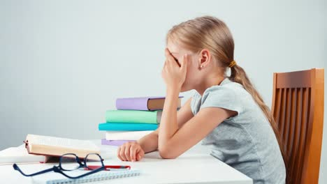 Student-Girl-7-8-Years-Sitting-In-The-Table-And-Sadly-Looking-At-Camera