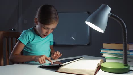 Very-Cheerful-Girl-Child-7-8-Years-Old-Using-Tablet-In-The-Night-In-Her-Desk