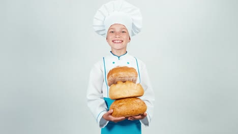 Young-7-8-Years-Old-Baker-Holds-Three-Loaves-Of-Bread-And-Looking-At-Camera