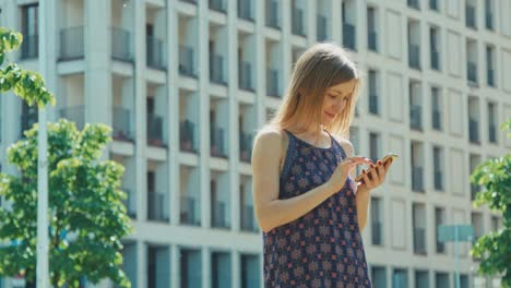 Young-adult-using-mobile-phone-outdoors-and-smiling-at-camera