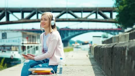 Young-Adult-Woman-In-Headphones-Using-Mobile-Phone-Outdoors-On-City-Quay