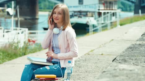 Young-Adult-Woman-Speaking-By-Mobile-Teléfono-And-Using-Tablet-PC-Outdoors-Smiling