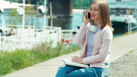 Young-woman-speaks-on-mobile-phone-and-uses-tablet-outdoors