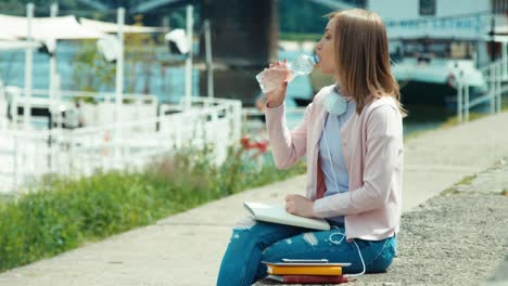 Young-Adult-Woman-With-Headphones-Drinking-Water-Outdoors-Smiling-At-Camera