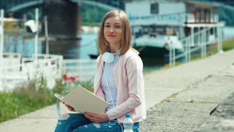 Junge-Erwachsene-Frau-Mit-Kopfhörern-Liest-Buch-Im-Freien-Und-Lächelt-In-Die-Kamera