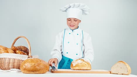 Young-Baker-Girl-7-8-Years-Cutting-Loaf-Of-Bread-Isolated-On-White