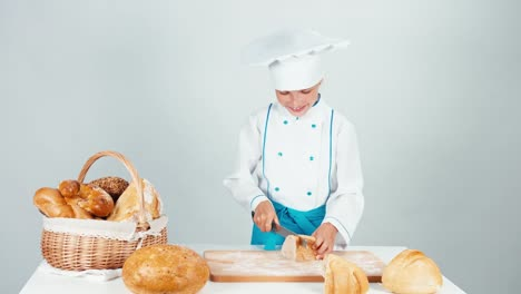 Young-Baker-Girl-7-8-Years-Cutting-Loaf-Of-Bread-On-The-Kitchen-Table-Isolated